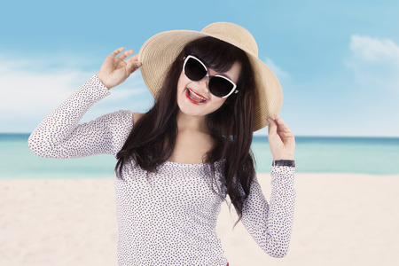 Portrait of excited young woman with long hair, smiling at the camera while wearing sunglasses and hat on the beach photo