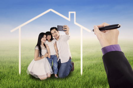 dream vision: Little happy family taking self photo together on the meadow under a dream home Stock Photo
