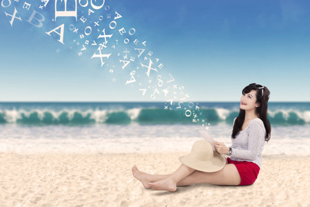 indonesian people: Portrait of cheerful woman sitting on the sand at the beach while using tablet and smiling happy