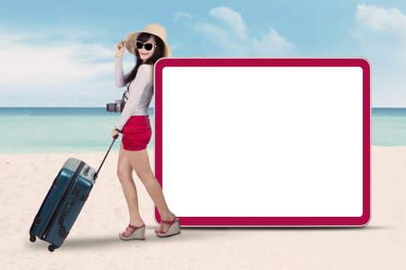Portrait of pretty woman carrying a suitcase and digital camera, standing at beach near the empty signboard photo