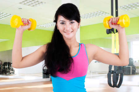 asian bodybuilder: Attractive healthy woman exercising with two dumbbell in the gym center