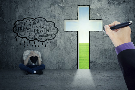 persona pensando: Persona sola pensando que su problema mientras est� sentado cerca de una cruz