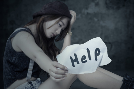 vagabundos: Retrato de solitaria adolescente sentado solo con la expresión deprimida y que muestra un papel con un texto de ayuda