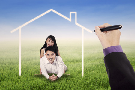 asian family home: Portrait of two happy couple lying on grass under a dream house Stock Photo