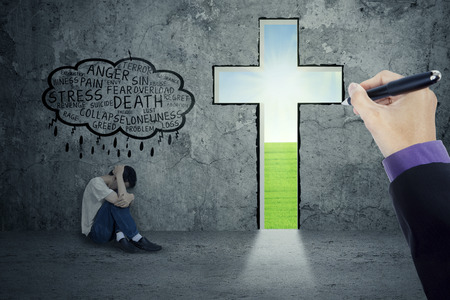 repentance: Depressed person thinking his problem with a hand drawing a cross in a wall