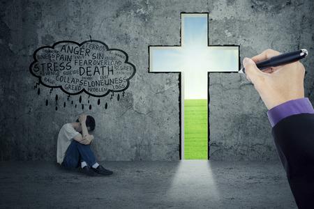 depresión: Persona deprimida pensando que su problema con una mano que dibuja una cruz en una pared