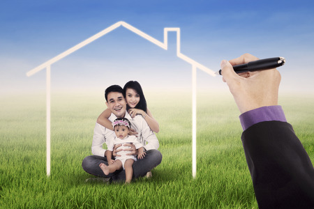 dream house: Little happy asian family sitting on the meadow while smiling at the camera under a dream home Stock Photo