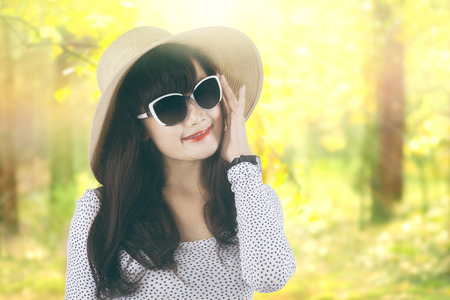 Portrait of beautiful woman standing in the autumn forest while wearing a sunglasses and hat photo