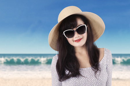 Portrait of young asian girl with long hair, wearing a sunglasses and hat, smiling at the camera on beach photo