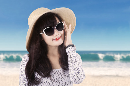 Closeup of female model wearing a sunglasses and hat at the beach photo
