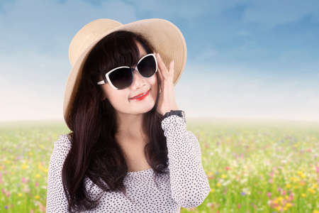 Portrait of young girl standing on the meadow while wearing sunglasses and hat photo