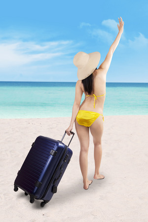 sexy asian woman: Beautiful asian woman with suitcase and swimsuit at the beach