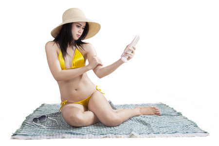 Portrait of attractive young lady wearing swimsuit while sitting on mat and using sun cream, isolated on white Stock Photo