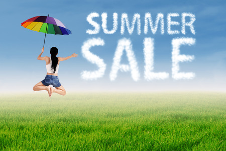 Summer sale clouds and woman jumping over green meadow photo