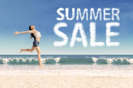 Summer Sale nuages ??et femme sautant sur la plage Banque d'images