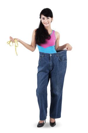 erfolgreiche frau: Erfolgreiche Frau verliert ihr Gewicht, in ihrer alten Jeans, w�hrend ein Messbandhalte