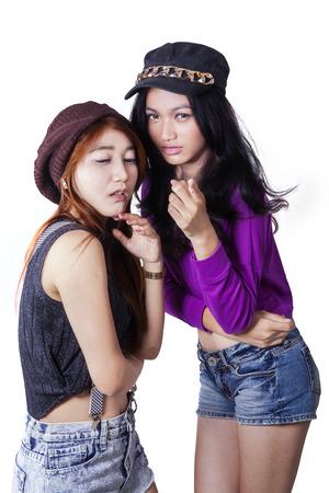 gossiping: Portrait of modern teenage girls gossiping someone in the studio, isolated on white Stock Photo