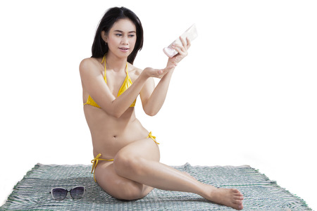 sexy asian girl: Young asian lady wearing sexy bikini while sitting in studio and using sunscreen, isolated on white