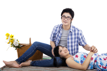 lovely couple: Portrait of young asian couple sitting on mat in the studio, isolated on white background