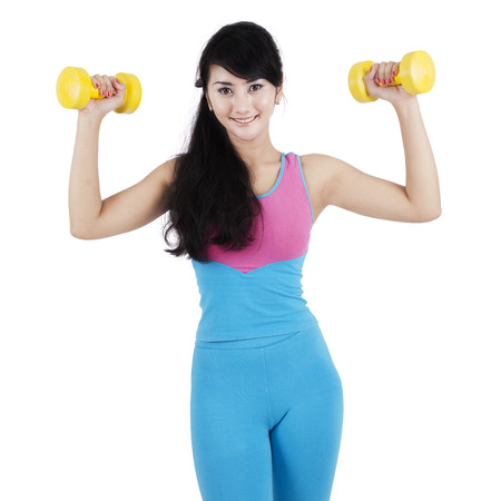 asian bodybuilder: Beautiful young fitness trainer use two dumbbells to train her arms muscle, isolated on white