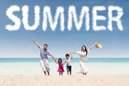 indian summer seasons: Cheerful young family enjoy holiday on the tropical seaside under a summers cloud Stock Photo