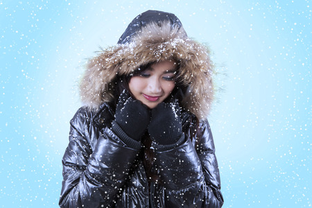fur hood: Portrait of pretty girl wearing jacket with fur hood and blue background