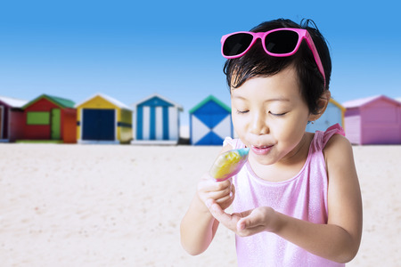 pink bikini: Closeup of little child eats a melt ice cream on the shore while wearing swimwear Stock Photo