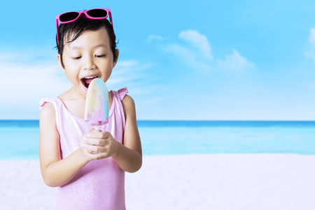 child ice cream: Attractive little child with swimsuit and sunglasses enjoy ice cream on the beach