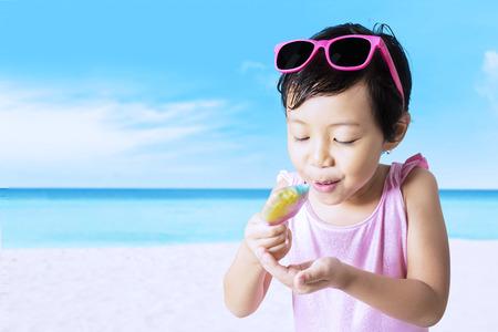 child ice cream: Portrait of little girl enjoy a melt ice cream on the beach while wearing swimwear