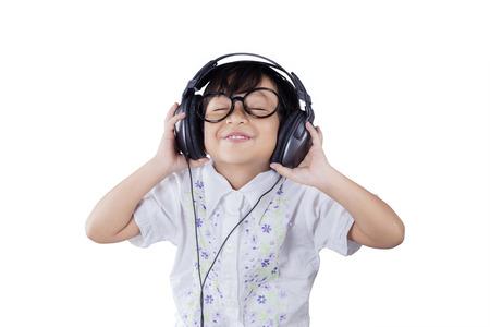 헤드폰으로 음악을 듣고있는 동안 안경을 쓰고 아름다운 아가씨의 초상 스톡 콘텐츠