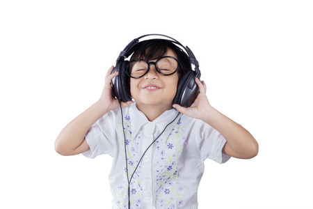 listening music: Portrait of beautiful little girl wearing a glasses while listening music with headphones