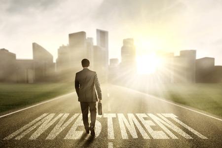 Homme d'affaires prospère et une mallette de marche sur la route avec un texte d'investissement