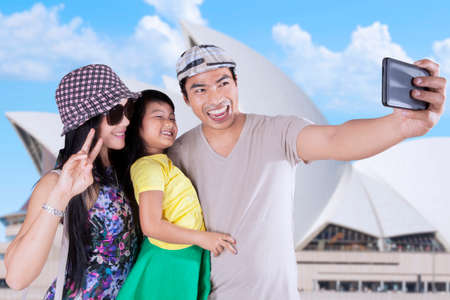family picture: Cheerful asian family enjoying holiday by taking self portrait at Opera House in Sydney