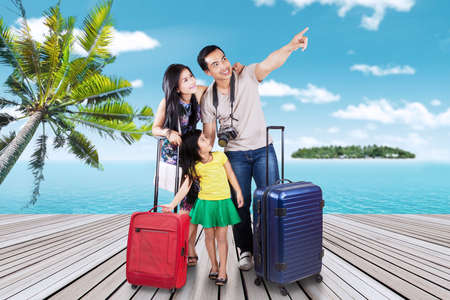 tourist resort: Portrait of happy family arriving at the pier of the resort island while carrying their suitcase