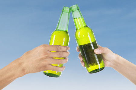 hand grip: Closeup of hands toasting with bottles of beer