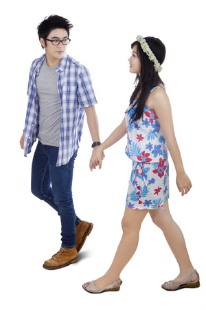 people walking white background: Portrait of two young couple walking in the studio while smiling and holding hands together, isolated on white Stock Photo