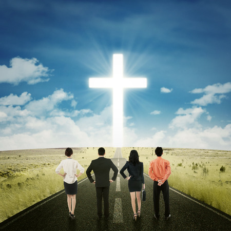 god walking: Rear view of successful businesspeople standing on the road while looking at a cross Stock Photo
