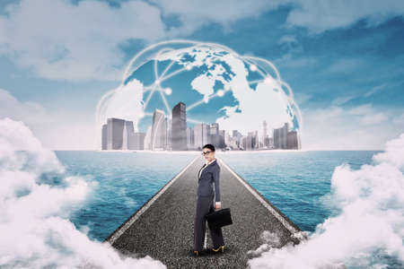 future city: Young businesswoman standing on the road with cityscape on a horizon Stock Photo