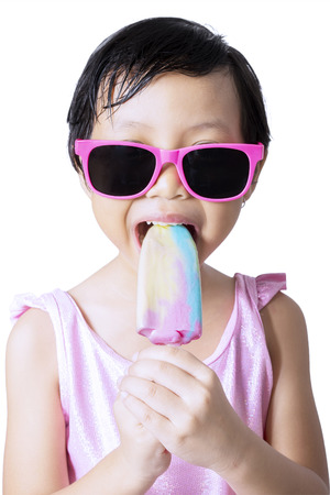pink bikini: Happy little girl wearing swimsuit and sunglasses in the studio while eating a fresh ice cream