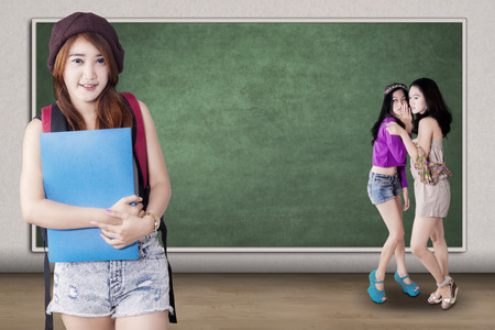 mockery: Portrait of confident female student standing in the class though she gets mockery