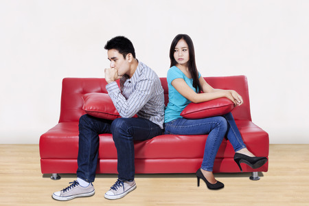 Couple sitting back to back after a fight on the sofa Stock Photo