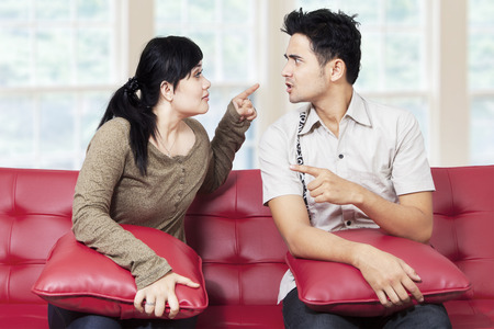 aggressive people: Portrait of asian couple sitting on sofa at home and quarreling