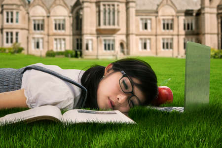 taking a break: Female college student sleeping on the grass at campus