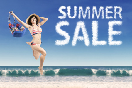 Beautiful female model wearing bikini and jumping at beach with summer sale cloud photo