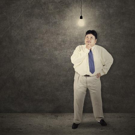 portly: Fat businessman looking at bright lightbulb symbolizing bright solution