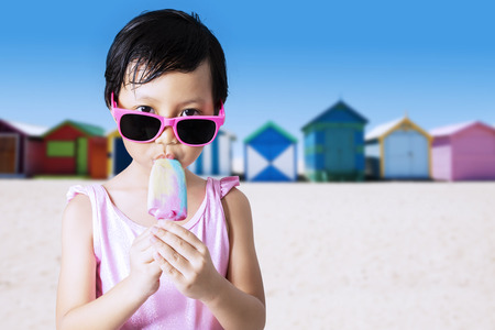 pink bikini: Portrait of lovely little kid wearing sunglasses and swimsuit on the beach while enjoy ice cream