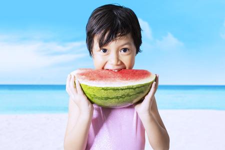 ni�as peque�as: Hermosa ni�a llevaba traje de ba�o en la playa mientras se come una sand�a fresca Foto de archivo