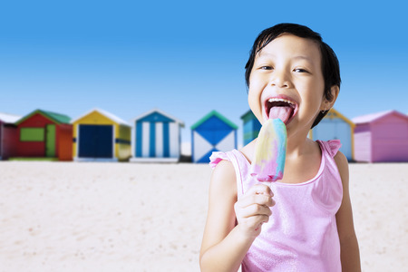 Closeup of pretty little girl wearing bikini with pink color, standing on the beach while eating ice cream Archivio Fotografico