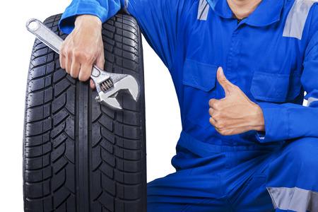 親指を現してタイヤとレンチ、保持している青い制服男性メカニックのクローズ アップ