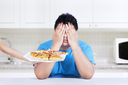 デブ男がジャンク フードを食べることを拒否すること。自宅キッチンでの撮影